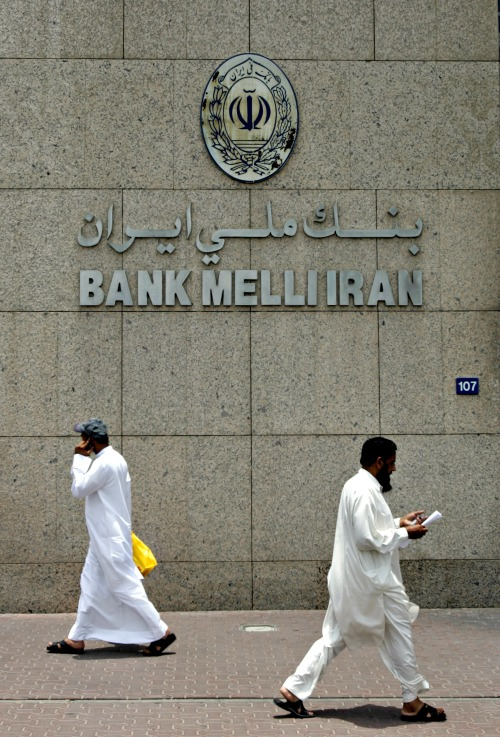 Two men pass by the main branch of Bank Melli Iran, the National Bank of Iran, in Dubai, United Arab Emirates, during July 2008