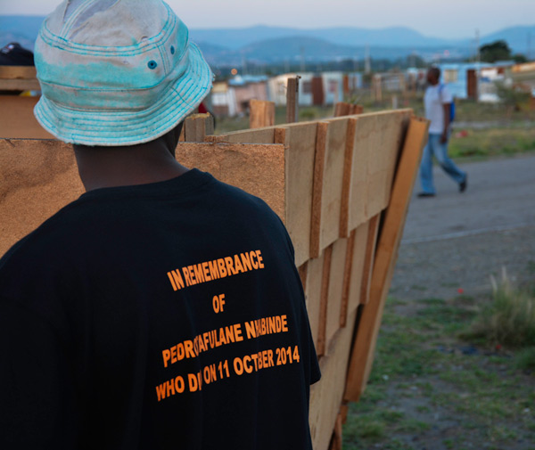 A South African miner wears a t-shirt marking a recent death at Aquarius Platinum's Kroondal mine