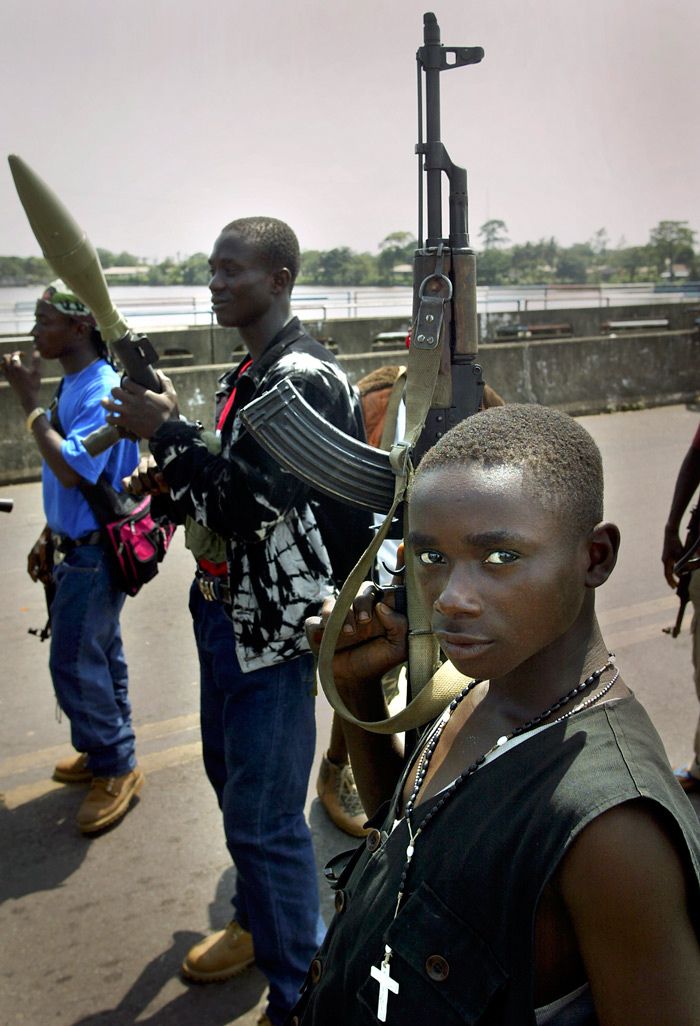 Soldiers stand guard on a bridge in Liberia during fighting in 2003