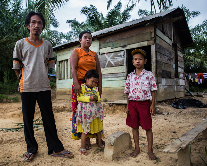 Revan Pragustiawan, aged 9, stands with his parents and one of two sisters before their home in Sungai Beruang