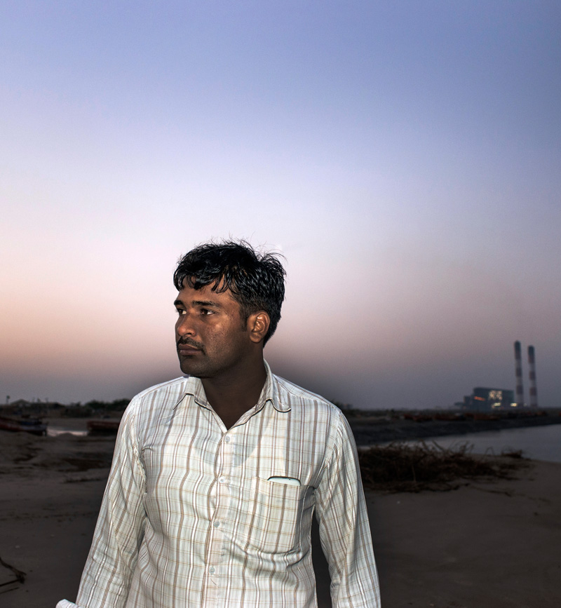 Gajendrasinh Jadeja stands in front of a coal-burning power plant financed by the World Bank Group