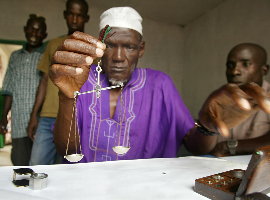 A legal dealer weighing diamonds in Koidu, Sierra Leone